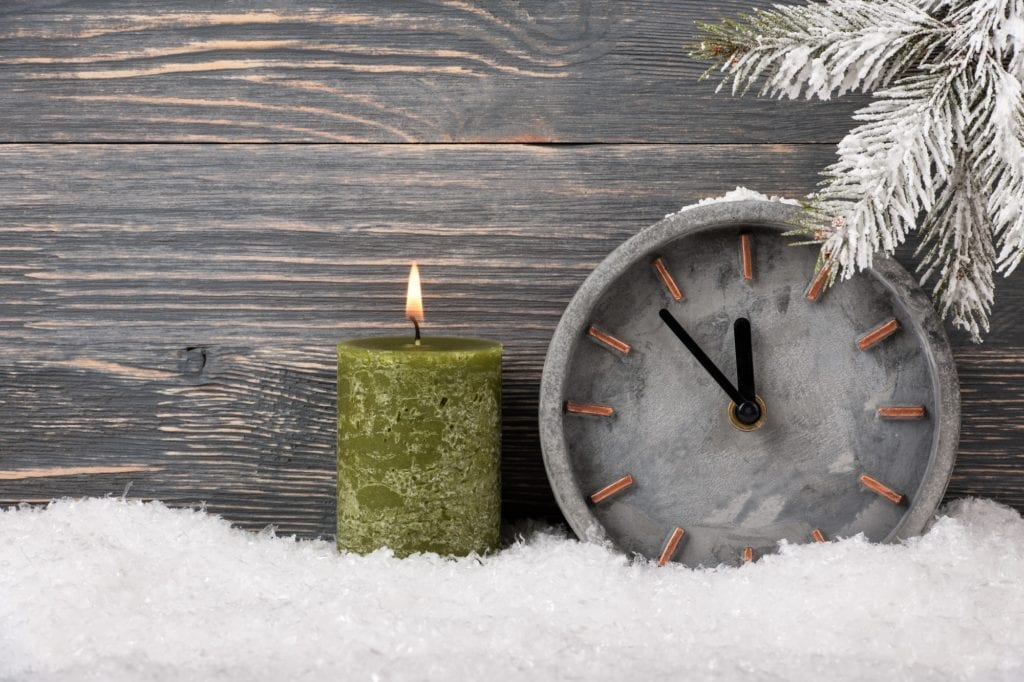 Christmas background with stone clock and candle