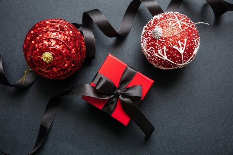 Christmas present and red xmas balls against black background, Black Friday Christmas concept.